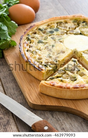 French quiche with vegetables on a rustic wooden table