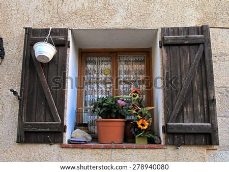 French rustic window with old wood shutters and flower pot in stone rural house, Provence, France. - stock photo