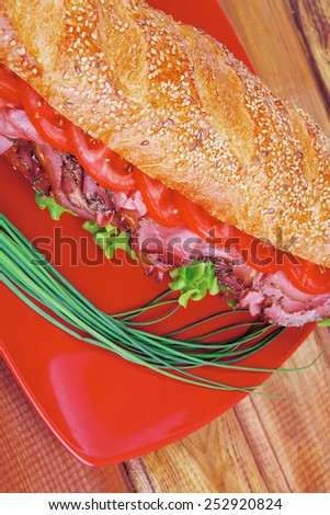 french sandwich : fresh white baguette with chicken smoked sausage on red ceramic plate over wooden table - stock photo