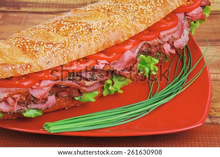 french sandwich : fresh white baguette with chicken smoked sausage over red plate on wood - stock photo