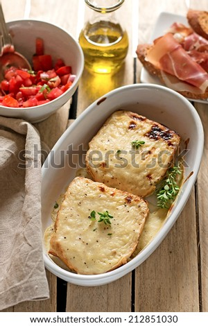 French sandwiches Croque-Monsieur with bechamel sauce, tomato salad and prosciutto ham. Shallow depth of field - stock photo