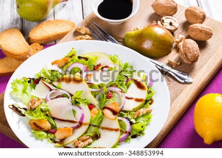 french style pear salad with walnut, fried chicken meat. red onion, lettuce leaves and cranberry on the white dish with caramelized balsamic sauce with toasts, selective focus, close-up - stock photo