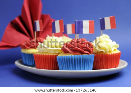 French theme red, white and blue mini cupcake cakes with flags of France and fleur-de-lis red napkin for holidays of France, Bastille Day, the Fourteenth of July. Close up with shallow DOF bokeh. - stock photo