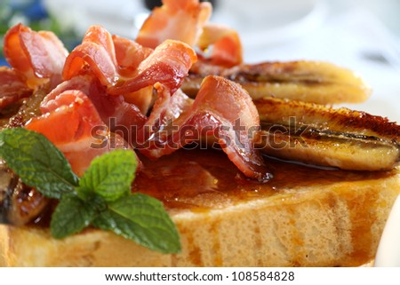 French toast with bacon and caramalized banana with maple syrup. - stock photo