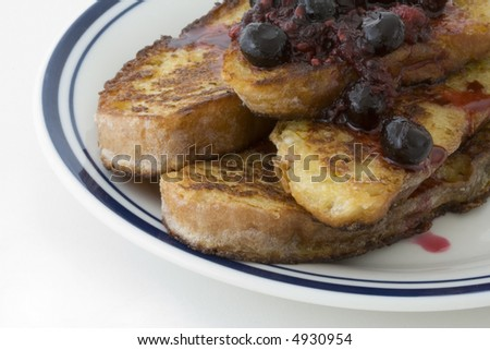 French toast with berry sauce on a white plate with blue rim, on white background, close-up - stock photo