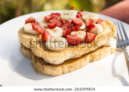 French toast with fresh fruit served outdoors on a white plate