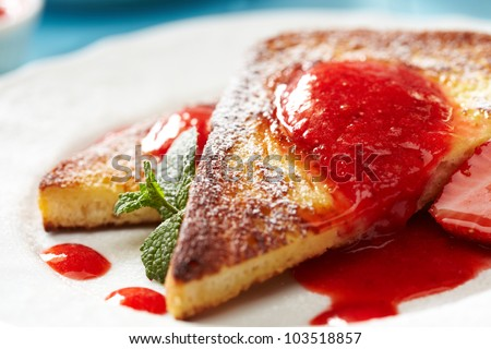 French toast with powdered sugar, strawberry sauce and mint