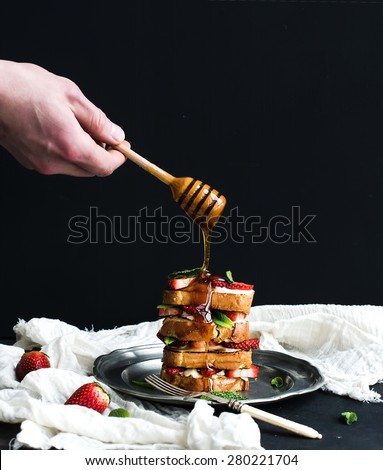 French toasts tower with strawberry, cream cheese and mint, hand is pouring honey over top of it. Dark background - stock photo