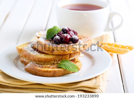 French toasts with icing sugar and berries, cup of tea - stock photo