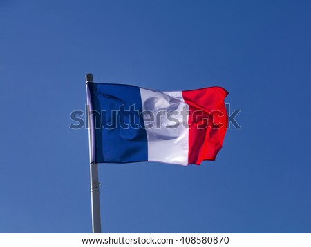 French tricolore flag; French flag flying in stiff breeze against clear summer sky  - stock photo