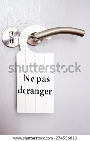 "French white signal of  ""do not disturb"" hanging on a door handle of hotels - stock photo"