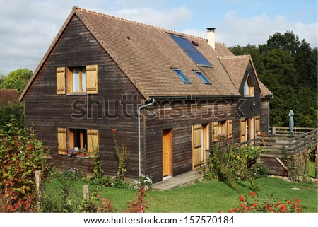 French Wooden House with Solar Panels and shutters - stock photo