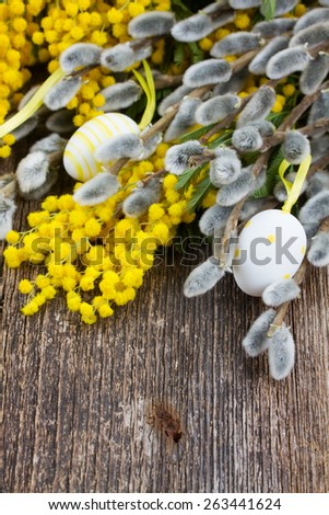 French yellow mimosa and catkins with easter eggs on wooden table - stock photo