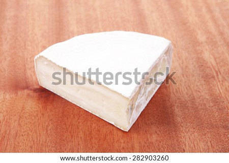 fresh aged french gouda cheese on wooden table - stock photo