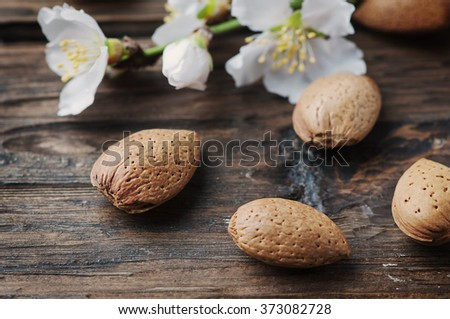 Fresh almond and flowers on the wooden table, selective focus - stock photo
