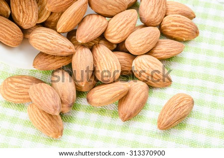 Fresh almond in white bowl on tablecloth. - stock photo