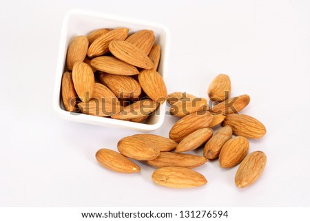 Fresh almonds spill out of bowl - stock photo