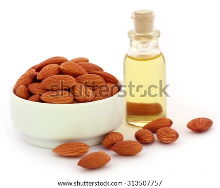 Fresh almonds with bottle of oil over white background