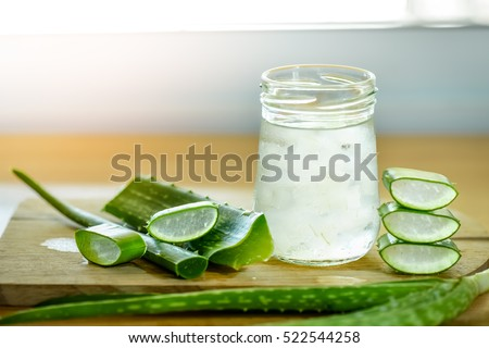 fresh aloe vera leaves and glass of aloe vera juice on wooden background