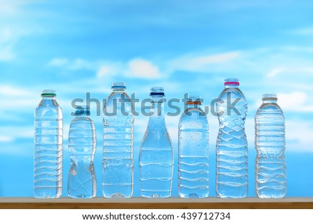 Fresh and clean drinking water in assortment of uncapped bottles with water droplet on sky background - stock photo