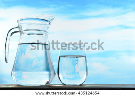 Fresh and clean drinking water in jug and glass on sky background - stock photo