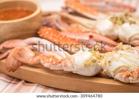 Fresh and delicious steamed or boiled jumbo crabs with hot chili sauce on wooden plate for seafood cuisine background - stock photo