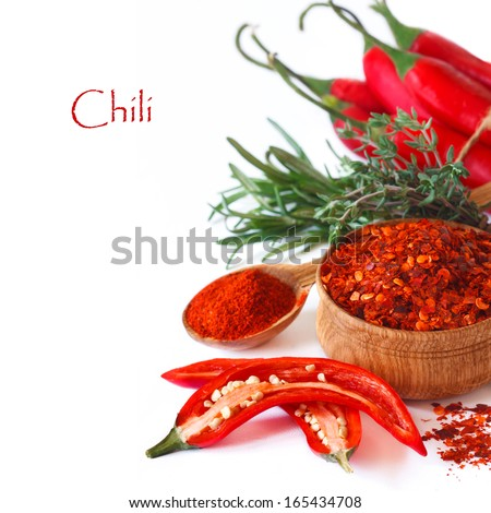 Fresh and dried hot chili peppers with herbs on a white background. - stock photo