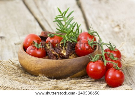 fresh and dried tomatoes on wooden background - stock photo