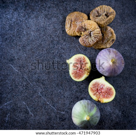 Fresh and dry figs on top of marble table. Space for text