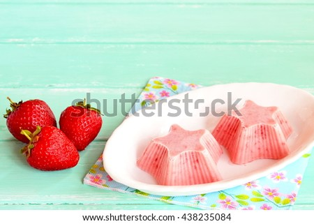 Fresh and flavorful strawberry ice cream on a plate. Frozen sweet strawberry yogurt shaped star. Easy healthy berry summer dessert. Fresh strawberries on wooden background - stock photo