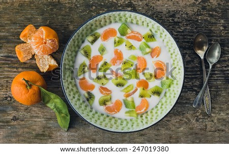 Fresh and healthy breakfast set: a bowl of yogurt with fresh kiwi and mandarins over a rough wooden desk. Top view - stock photo