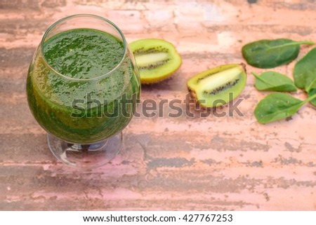 Fresh and healthy green smoothie on wooden background