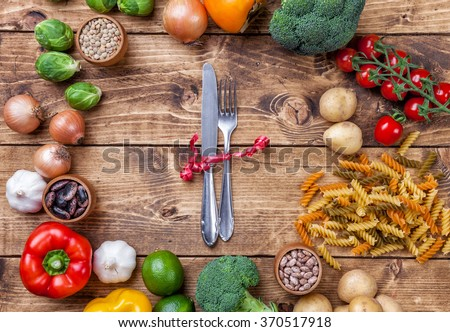 Fresh and healthy organic vegetables and food ingredients on wooden background - stock photo
