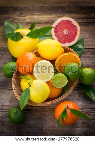 Fresh and juicy citrus fruits in the basket on the rustic table - stock photo