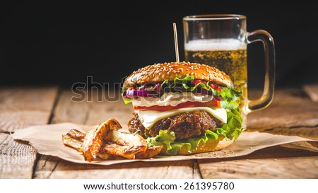 Fresh and juicy hamburger on a paper pad with a beer on a wooden table. - stock photo