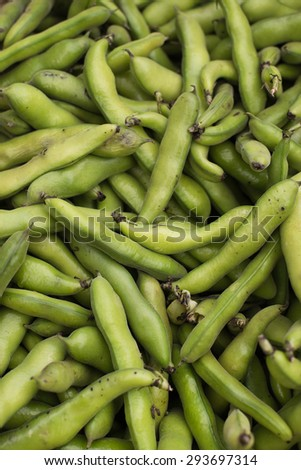 fresh and organic fava or broad beans at farmers market in Vancouver, BC. texture as background, vertical. - stock photo