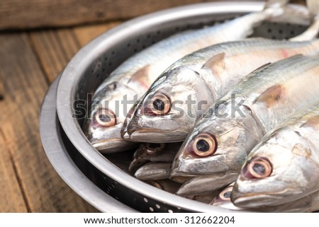 Fresh and raw silver tuna or mackerel fishes in stainless bowl on wood table for food preparation background - stock photo