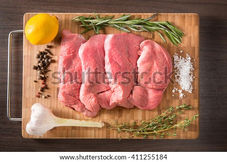 Fresh and raw veal meat. Steaks with seasonings in a row ready to cook. Bamboo and wooden board background. overhead view - stock photo
