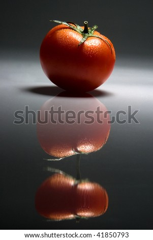 Fresh and red tomato, reflected  on a dark background - stock photo