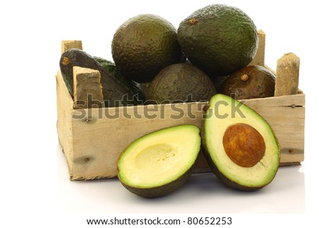 fresh and ripe avocado's and a cut one in a wooden crate on a white background