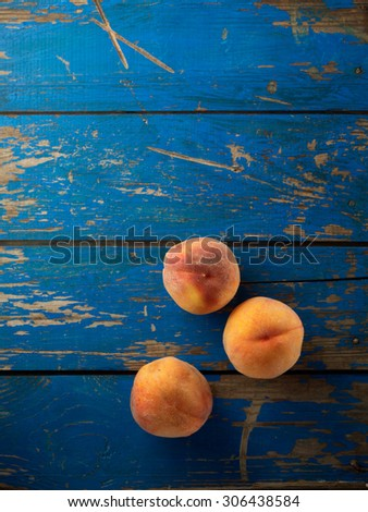 Fresh and ripe organic peaches on the blue wooden table. Top view. - stock photo