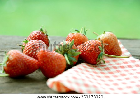 Fresh and ripe strawberries on a wooden background (selective focus) - stock photo