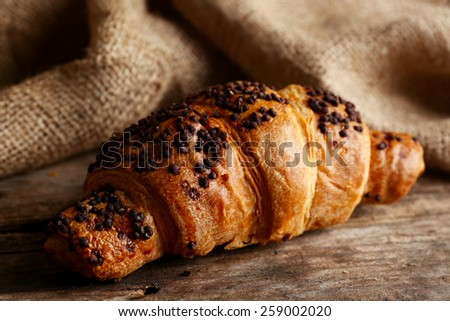 Fresh and tasty croissant with chocolate on wooden background - stock photo