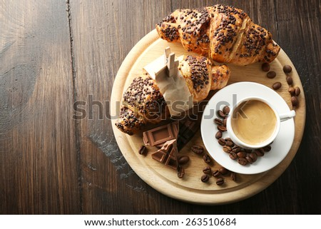 Fresh and tasty croissants with chocolate and cup of coffee on wooden background - stock photo