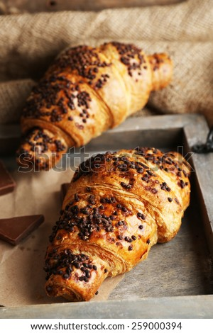 Fresh and tasty croissants with chocolate on wooden tray, on sackcloth background - stock photo