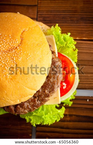 fresh and tasty hamburger with cheese on wood background.