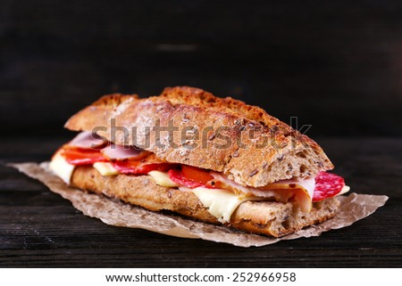 Fresh and tasty sandwich with ham and cheese on paper on wooden background - stock photo