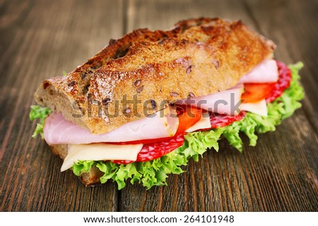 Fresh and tasty sandwich with ham and vegetables on wooden background - stock photo