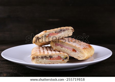 Fresh and tasty sandwiches on plate on wooden background - stock photo