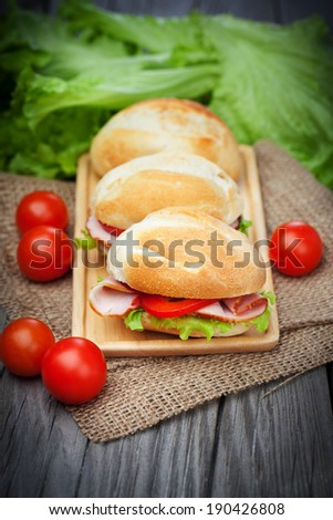 Fresh and tasty sandwiches with ham, tomatoes and fresh green lettuce on wooden table - stock photo